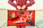 Woman holds suitcase with stamps flags — Stok fotoğraf