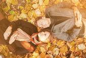 Loving couple lying on autumn leaves — Stock Photo