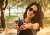 Woman showing a fir cone — Stock Photo
