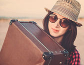 Hipster girl traveler with suitcase — Stockfoto