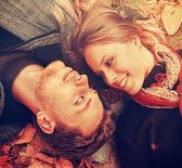 Smiling loving couple in autumn leaves — Stock fotografie
