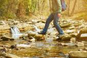 Man with backpack crossing river — Stock Photo