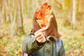 Woman with yellow oak leaf — Stock Photo