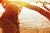 Woman looking at city from hill — Stock Photo