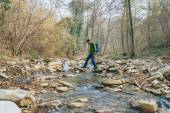 Hiker man crossing  river — Stock Photo