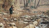Hiker woman crossing river — Stock Photo