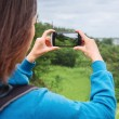 Woman taking photographs of summer landscape — Stock Photo #66583627