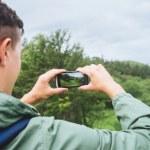 Hiker man taking photographs of landscape — Stock Photo #66583631