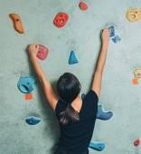 Sporty woman climbing up on rock wall — Photo