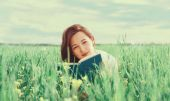 Woman with book on summer meadow — Stock Photo