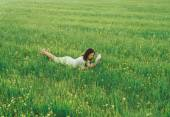 Girl lying on meadow with book — Stok fotoğraf