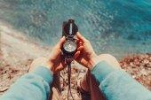 Traveler holding a compass on coastline — Stock Photo