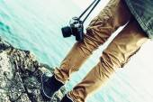 Woman with old camera standing on coast — Stock Photo