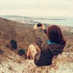 Girl taking photographs landscape with phone — Stock Photo #73888541