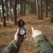 Hiker with compass pointing direction in forest — Stock Photo #73888565