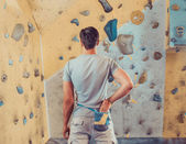 Man standing in front of practical climbing wall — Stock Photo