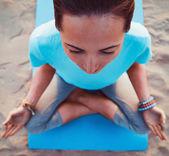 Mulher meditando na posição de lótus na praia — Fotografia Stock