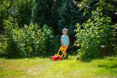 Happy small boy help with gardening with his lawn mower — Stock Photo