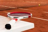 Tennis racket on the table, clay court, tennis net and ball — Stock Photo