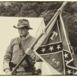 Civil war confederate soldier holding a flag aged to sepia — Stock Photo #57730257