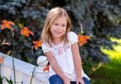 Cute little girl sitting on a rail — Foto Stock