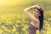 Belle femme dans une prairie de fleurs jaunes avec les mains vers le haut — Photo