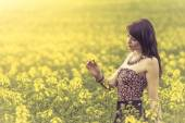 Beautiful woman in meadow of yellow flowers looking at flower — Stock Photo