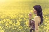 Beautiful woman in meadow of yellow flowers sniffing flower — Stock Photo