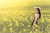 Beautiful woman in meadow of yellow flowers with arm up — Stock Photo
