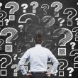 Businessman looking at question marks — Stock Photo #59761359
