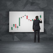 Businessman drawing candlestick chart — Stock Photo