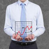 бизнесмен, держащий диаграммы — Стоковое фото