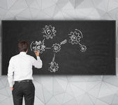 Businessman drawing cogs — Stock Photo