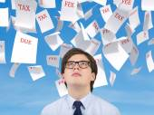 Man looking to falling tax papers — Stock Photo