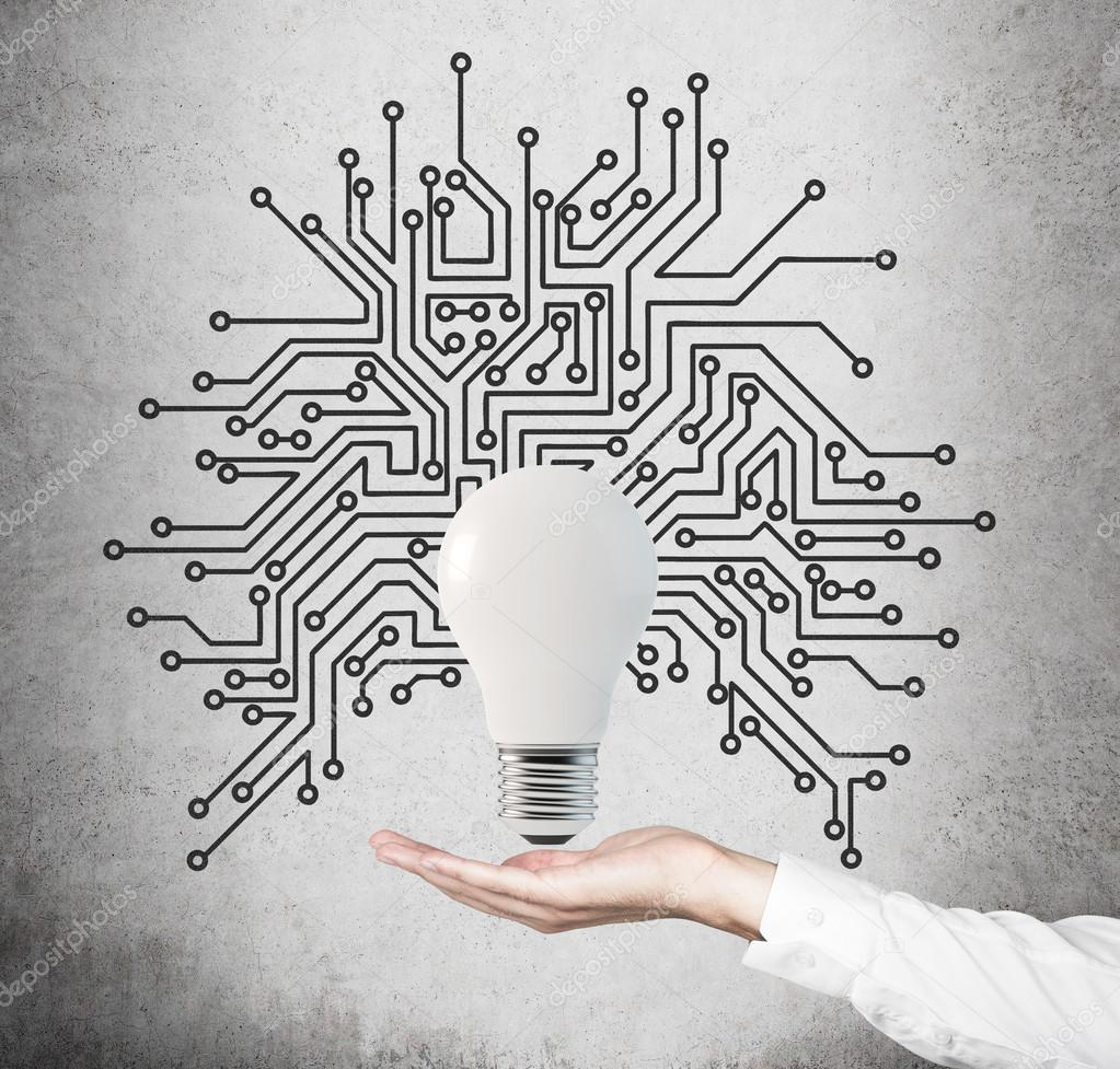 只手握住灯泡与微电路灰色背景
