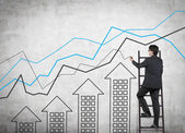 Businessman on ladder drawing charts — Stock Photo