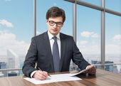 Handsome legal consultant is dealing with due diligence process in a modern skyscraper office with a panoramic New York view. — Stock Photo