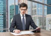Handsome legal consultant is dealing with due diligence process in a modern skyscraper office with a panoramic Moscow city view. — Stock Photo