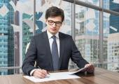 Handsome legal consultant is dealing with due diligence process in a modern skyscraper office with a panoramic Moscow city view. Pages of contract are falling down from the sky. — Stock Photo
