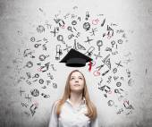 Young beautiful business woman is thinking about education at business school. Drawn business icons over the concrete wall. Graduation hat. — Stock Photo