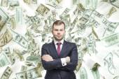 Young handsome businessman is standing over the falling down dollar notes. A concept of career success. — Stock Photo