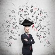 Young handsome businessman is thinking about education at business school. Drawn business icons over the concrete wall. Graduation hat. — Stock Photo #72441741
