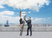 Young handsome businessman is holding a ladder for the lady in a formal clothes to boost her ideas. The concept of the success and team working. On the roof terrace in the Manhattan, New York. — Stock Photo