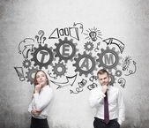 Business couple are thinking about cooperation in a business project. Drawn gears on the wall with the word team. The concept of the team working. — Stock Photo