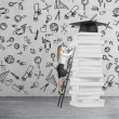 Young lady is climbing up to get university degree. Pile of books and a graduation hat as a prize. — Stock Photo #73477313