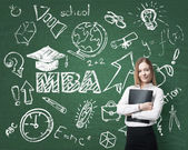 A lady is pondering over the business degree. A concept of the MBA degree. Drawn educational icons on the board. — Stock Photo
