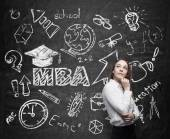 A lady is pondering over the business degree. A concept of the MBA degree. Drawn educational icons on the chalkboard. — Stock Photo