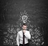 Young manager is thinking about new business ideas. Business icons and an yellow light bulb are drawn on the dark concrete wall. — Stock Photo