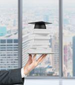 Студента рука держит гаджет с книгами и градации шляпу на нем. Панорамный вид на Нью-Йорк. — Стоковое фото