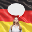Beautiful woman and the blank speech bubble above the head. German flag as a background. — Photo #74600273